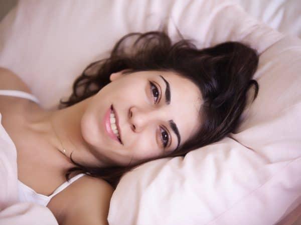 Frau lächelt und liegt im Bett