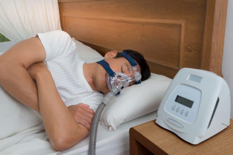Mann mit Schlafmaske im Bett
