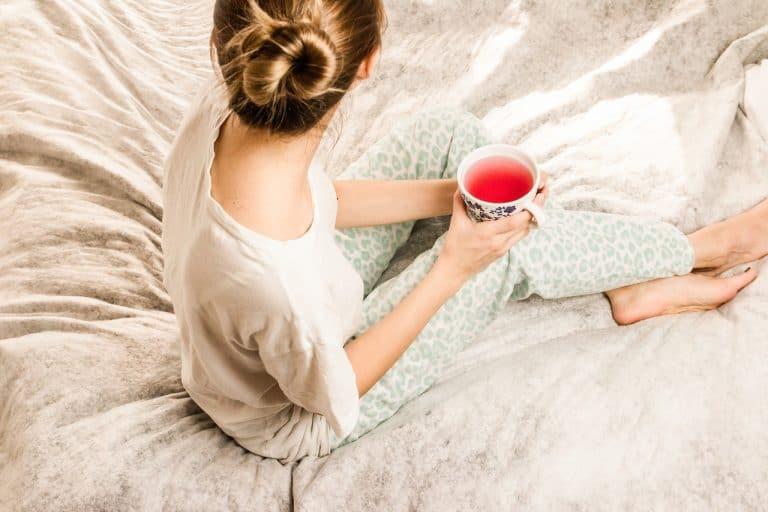 Frau sitzt mit Tee auf Bett