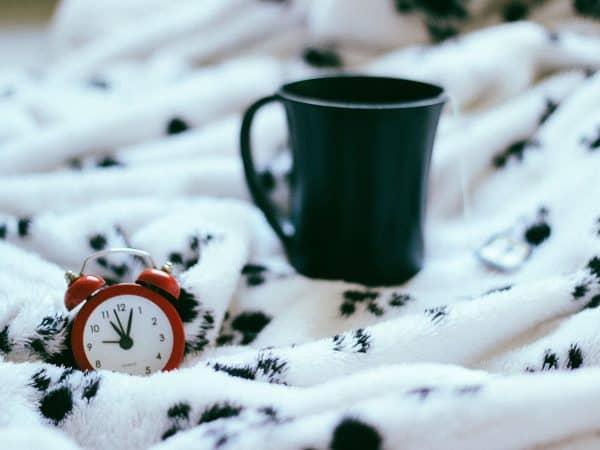 Tasse und Wecker auf dem Bett